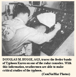 DOUGLAS M. BUGGE, AG3, traces the feeder bands of Typhoon Karen on one of the radar consoles.